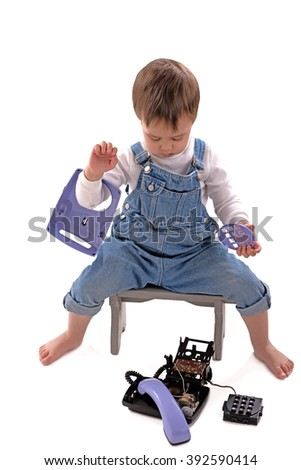 the child sits on a chair and considers the broken telephone apparatus