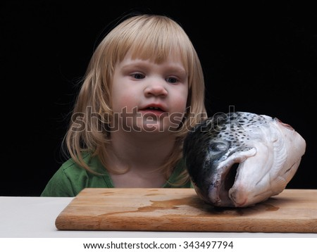 The child stares at a huge fish head. Fish on the table, on a cutting board. The child is small, a large fish head. Fish for soup (fish soup). black Background - stock photo