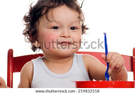 The child studies independently to eat. - stock photo