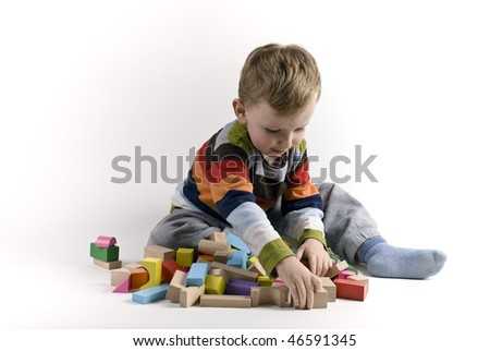 The child the boy plays cubes on a white background