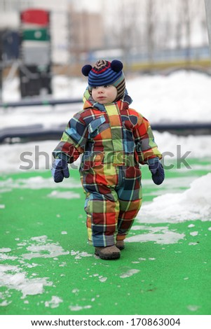 The child walking at playground in winter - stock photo