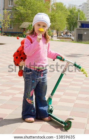 The child with a skateboard, smells a flower