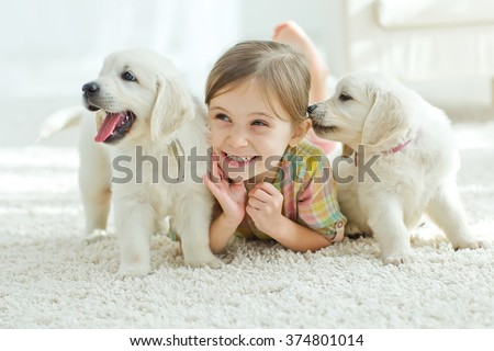 The child with the dog lying on the mat at home - stock photo