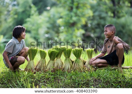 The children are smiling while they are resting beside rice sprouts. - stock photo