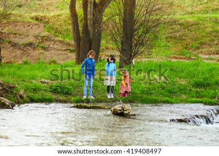 The children happy outdoors sitting on river.