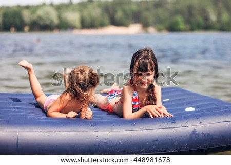 The Children rest and float on mattresses. - stock photo
