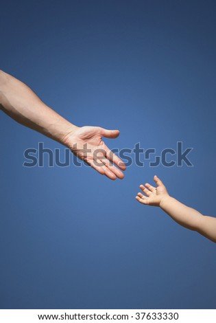 The children's hand reaches for a daddy's hand against the blue  sky