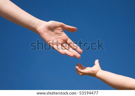 The children's hand reaches for a mother's hand against the blue  sky