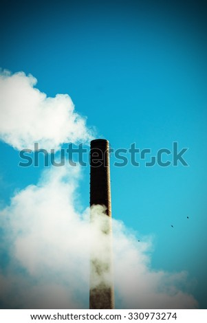 The chimney and plenty of white smoke against a blue sky in Finland. The photograph also has a flying bird. Image includes a effect.