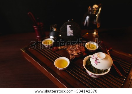 The Chinese tea items. Porcelain gaiwan, three cups with tea, pancake of traditional Chinese puer tea, siphon and golden frog on tea desk. Soft selective focus.