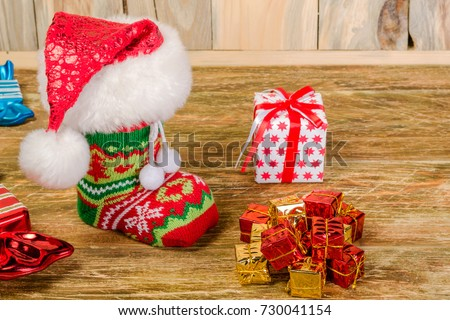 The Christmas stocking, covered with Santa's cap, is on a scratched wooden table. Nearby lie decorative candy and a hill of gifts. Close-up.