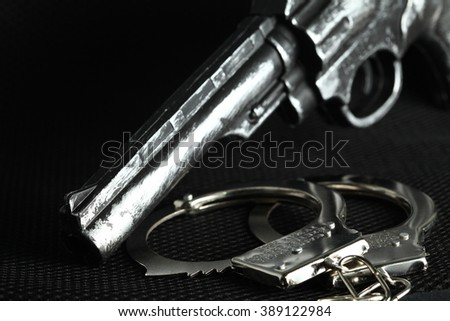 The chrome metal handcuffed and plastic toy gun represent the crime fraud and punishment equipment concept related idea.