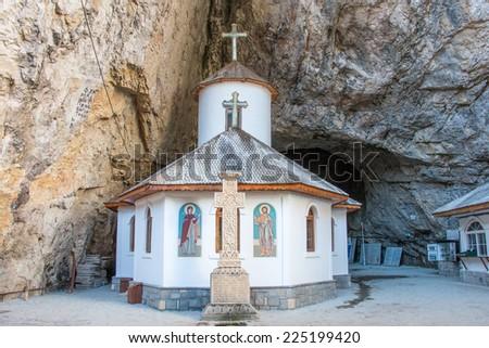 The church at the entrance of Ialomita cave in Bucegi mountains, Romania. - stock photo