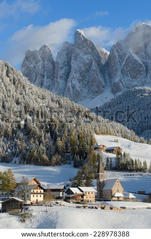 The church of St. Magdalena or Santa Maddalena, a village in front of the Geisler or Odle dolomites mountain peaks in the Val di Funes (Villnoesser Tal) in South Tyrol in Italy in winter. - stock photo