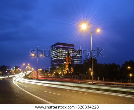 The church, on the background of  office building, the highway in the city of Katowice, Poland, in the evening. - stock photo