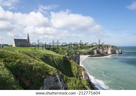 The church on the top of hill with the background of elephant shaped cliff, Etretat, Normandy, France - stock photo