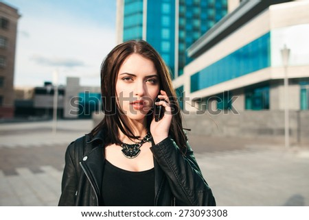 the city concentrated woman speaks by phone on the street - stock photo