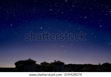 The city is under dark sky and stars - stock photo
