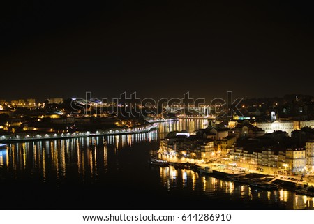 The city lights and reflections in the Douro river at night in Porto, Portugal.