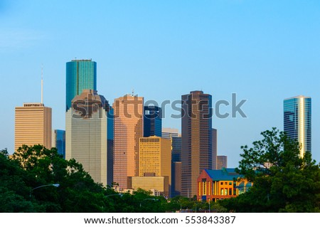 The city of Houston, TX skyline is illuminated by a setting sun and framed by green trees