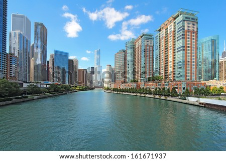 The city skyline along the Chicago River in Chicago, Illinois against a bright blue sky with white clouds