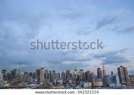 The cityscape of Midtown Manhattan and Piers viewed from the Hudson River at sunset in New York City, USA.
