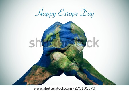 the clasped hands of a young man patterned with a europe map (furnished by NASA) and the text happy europe day - stock photo
