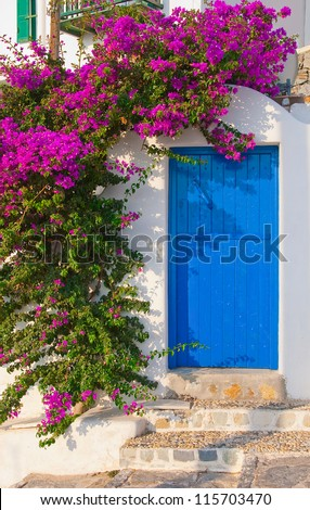 The classical architecture of the Greek cities - with its narrow streets, blue door on the white buildings and flowers at the entrance! - stock photo