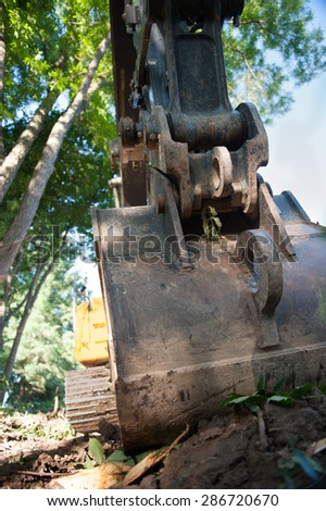 The claw of a front-loader devastates the vegetation growing in a residential neighborhood