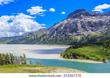 The clean blue mountain water enters the muddy waters of Middle Waterton Lake at Waterton Lakes National Park in Alberta, Canada. - stock photo