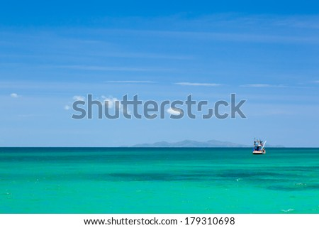 The clear green and blue sea with a fishing boat - stock photo