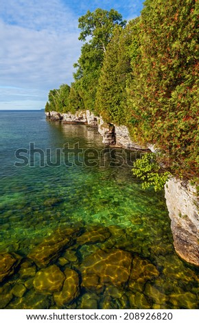 The clear water of Lake Michigan meets the rugged and rocky coastline of Cave Point in Door County, Wisconsin. - stock photo