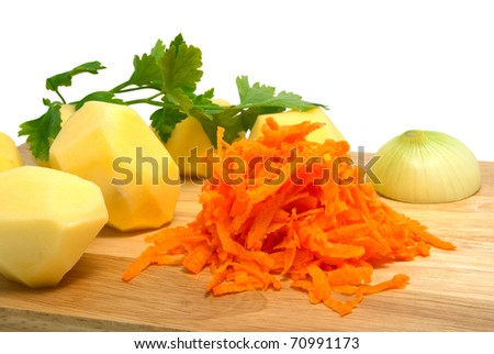 The cleared potato, onions and grated carrots on a chopping board. Components for soup - stock photo