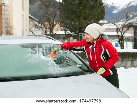 The clearing of automobile wind screen from hoar frost - stock photo