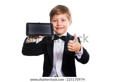 The clever boy, dressed in a tuxedo, holds a tablet in his hand, isolated - stock photo