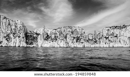 The cliffs of the famous Calanques national park of Cassis (near Marseilles in Provence, France). The storm is coming. Aged photo. Black and white. - stock photo