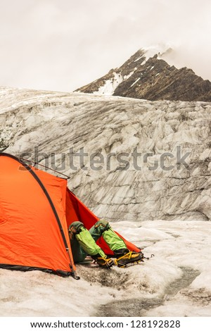 The climber lies in tent of mountain camp against beautiful top