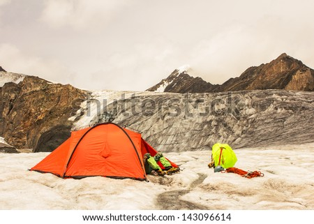The climber lies in tent of mountain camp with feet outside - stock photo