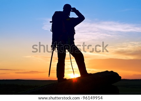 The climber on mountain top has raised hand to helmet and looks afar - stock photo
