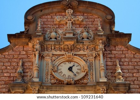 The clock on the facade at the entrance to the church of  monastery de Montserrat (mountain of Montserrat, Spain, Europe) - stock photo