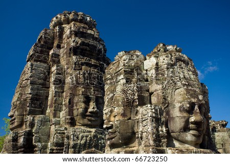 The close-up of heads and happy faces of the Bayon temple at eye-level against a beautiful blue sky at the Angkor Wat temple complex in Siem Reap, Cambodia