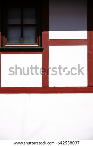 The close-up of the beam construction of a half-timbered house with window in strong sunlight / Half-timbered house facade with window
