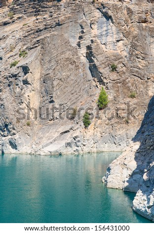 The close-up  of the rocks over the turquise water - stock photo