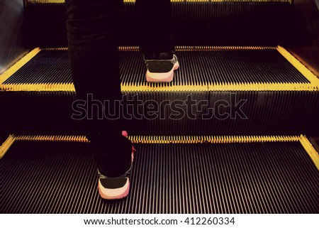 The close up shot of human walking on the escalator processing in low light tone with the black vignette in the corner - stock photo
