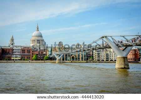 The closeup view of St. Paul's Cathedral and Millennium Bridge by Thames River in London, United Kingdom - stock photo