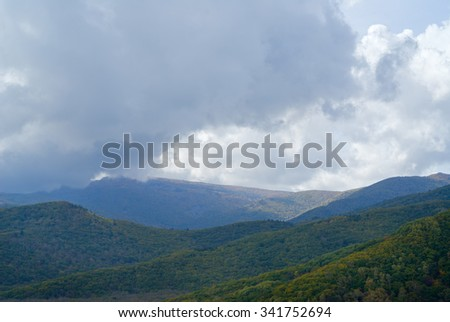 The cloudscape in taiga: mountains and cloudy sky. Early autumn.