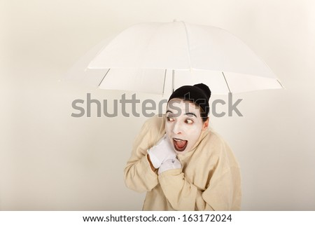 The clown holding a white umbrella in hand - stock photo