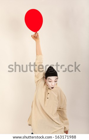 The clown is playing with red balloons - stock photo