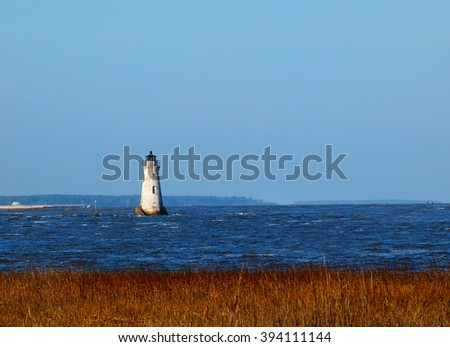 The Cockspur Island Lighthouse at the mouth of the Savannah River, part of the Fort Pulaski National Monument in southern Georgia, at high tide.  - stock photo