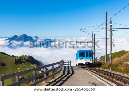 The cogwheel train for tourists running toward the top of Rigi mountain. Famous tourists place near Lucerne, Switzerland. With Pilatus above the clouds the background. - stock photo